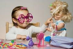 Kleines entzückendes Mädchen, das mit Puppe spielt Stockfotos
