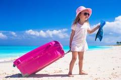 Kleines entzückendes Mädchen mit großem Gepäck in den Händen an Lizenzfreie Stockfotos