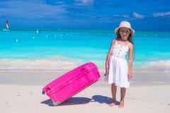 Kleines entzückendes Mädchen mit großem Gepäck in den Händen an Lizenzfreies Stockfoto