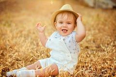 Kleines entzückendes molliges Baby in einem Strohhut und in einer weißen Klage Stockbild