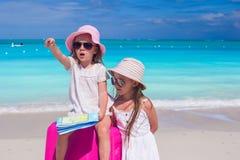 Kleines entzückendes Mädchen, das nach Weise mit einer Karte und einem großen Koffer auf dem Strand sucht Lizenzfreie Stockfotos