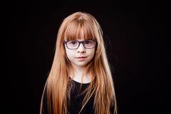 Kleines ernstes blondes Mädchen mit Gläsern auf einem schwarzen Hintergrund Stockfotografie