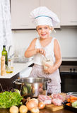 Kleines europäisches Mädchen, das Lebensmittel kocht Stockfotos