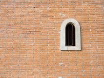 Kleines Fenster auf Backsteinmauer Stockbild
