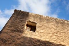 Kleines Fenster in der alten Steinwand, unter blauem Himmel Lizenzfreie Stockfotografie