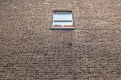 Kleines Fenster in einer großen Backsteinmauer lizenzfreie stockbilder