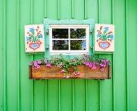 Kleines Fenster mit den Blumen gemalt Stockbilder