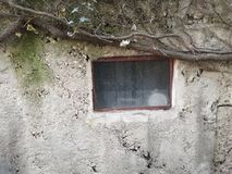 Kleines Fenster und Wand stockbild