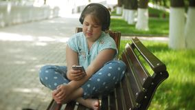 Kleines fettes Mädchen mit einem Tablet-PC und Kopfhörern, die auf einer Bank hörend Musik oder ein Video in einem Sommer aufpass stock footage