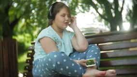 Kleines fettes Mädchen mit einem Tablet-PC und Kopfhörern, die auf einer Bank hörend Musik oder ein Video in einem Sommer aufpass stock video