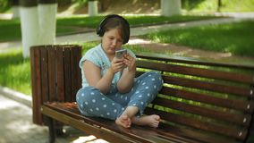 Kleines fettes Mädchen mit einem Tablet-PC und Kopfhörern, die auf einer Bank hörend Musik oder ein Video in einem Sommer aufpass stock video footage