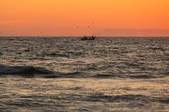 Kleines Fischerboot auf dem Ozean bei Sonnenuntergang lizenzfreie stockfotografie