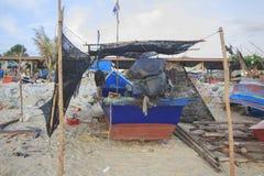 Kleines Fischerboot auf dem schmutzigen Strand Stockbilder