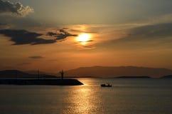 Kleines Fischerboot bringt Hafen mit Leuchtturm zurück Lizenzfreies Stockfoto