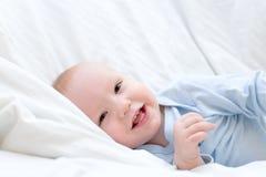 Kleines frohes Schätzchen, das auf Bett stillsteht Lizenzfreies Stockbild