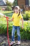 Kleines Gärtnermädchen, das mit Schlauchleitung wässert lizenzfreie stockbilder