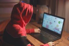 Kleines Gamerkind in der Haube, die das Massenmultispielerspiel on-line auf Laptop spielt lizenzfreie stockfotografie