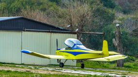 Kleines gelbes Flugzeug nahe seiner Garage lizenzfreie stockfotos