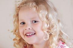 Kleines gelocktes blondes kaukasisches Mädchen, das träumerisch den Abstand untersucht Lizenzfreies Stockfoto