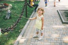 Kleines gelocktes blondes Mädchen, das draußen spielt Lizenzfreie Stockfotografie