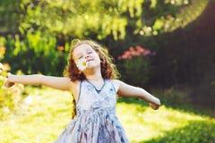Kleines gelocktes Mädchen, das im Frühjahr Park stillsteht stockfoto