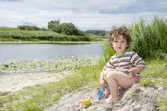 Kleines gelocktes Mädchen des Sommers, das mit einer Schaufel auf dem Riverbank spielt Lizenzfreies Stockbild