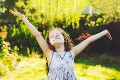 Kleines gelocktes Mädchen mit Gänseblümchen in ihren Zähnen, die im Frühjahr Park stillstehen stockfoto