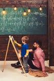 Kleines Genie, das Mathe lernt Helfendes Kind des Lehrers oder des Vaters, zum von Gleichung auf Tafel zu lösen Bärtiger Kerl im  stockfotografie