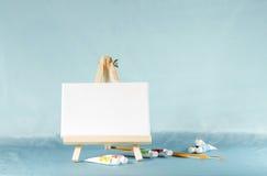 Kleines Gestell mit einem leeren Segeltuch auf einem blauen Hintergrund Stockbild