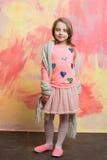 Kleines glückliches Baby im rosa Rock, im Schal und im Hemd Stockfotos