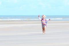 Kleines glückliches Mädchen, das auf dem Strand spielt Lizenzfreies Stockbild