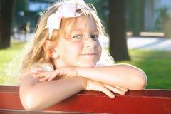 Kleines glückliches Mädchen, das im Sommerpark sich entspannt Stockfotos