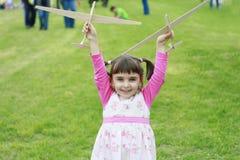 Kleines glückliches Mädchen, das mit zwei hölzernen Flugzeugen spielt Lizenzfreies Stockbild