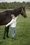 Kleines glückliches Mädchen in einer weißen Strickjacke, die den Pferdewarmen Herbsttag steht und umarmt Lebensstilporträt stockbild