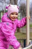Kleines glückliches Mädchen spielt auf dem Spielplatz des Kindes Lizenzfreies Stockfoto