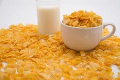 Kleines Glas von Milch und von kleiner Schale Corn Flakes umgeben durch Pil Stockfoto