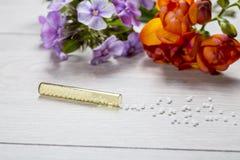 Kleines Glasrohr mit Homöopathiekügelchen stockfoto