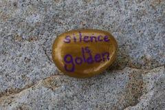 Kleines Gold gemalte Felsenzustände Reden ist Silber, schweigen ist Gold Lizenzfreie Stockfotos