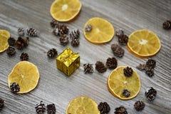 Kleines goldenes Geschenk mit dekorativen Kegeln Stockfoto