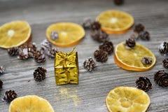 Kleines goldenes Geschenk mit dekorativen Kegeln Stockbilder