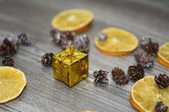 Kleines goldenes Geschenk mit dekorativen Kegeln Stockbild