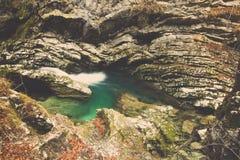 Kleines grünes Pool umgeben durch den großen Felsen bedeckt im Moos Stockfotos