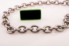 Kleines Grünes versah das schwarze noticeboard mit Seiten, das durch Kette auf weißem Hintergrund umgeben wurde lizenzfreie stockfotos