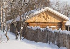 Kleines hölzernes Blockhaus in einem schneebedeckten Wald Stockbild