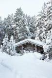 Kleines hölzernes Blockhaus im Schnee Lizenzfreies Stockfoto