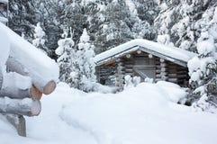 Kleines hölzernes Blockhaus unter weißem Schnee Stockfotografie