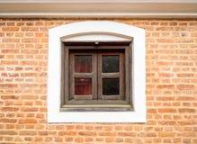Kleines hölzernes Fenster und Backsteinmauer Stockfotografie
