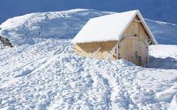 Kleines hölzernes Haus eingefroren im Schnee Stockbilder