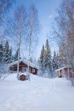 Kleines hölzernes Haus im Winterwald Lizenzfreie Stockbilder