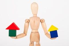 Kleines hölzernes Mannequin sitzen, buntes Blockhaus halten lokalisiert Stockbilder